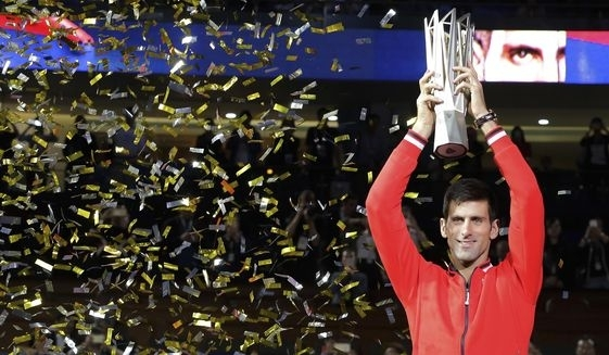 Novak Djokovic of Serbia holds up his winner's trophy after defeating Jo-Wilfried Tsonga of France
