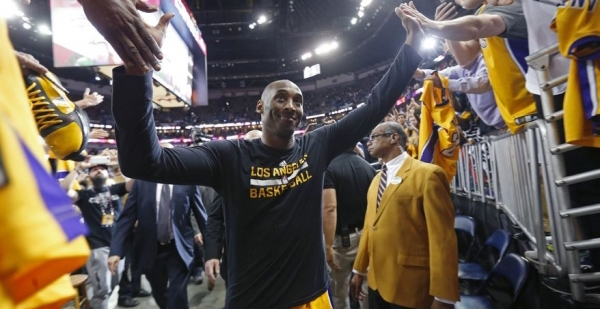 Los Angeles Lakers forward Kobe Bryant greets fans as he leaves the court after an NBA basketball game.